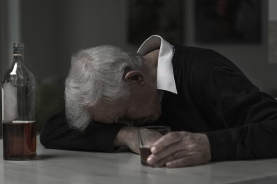Old retired man alcoholic sleeping on the table